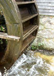 image of limited water-wheel against stone-wall with water below